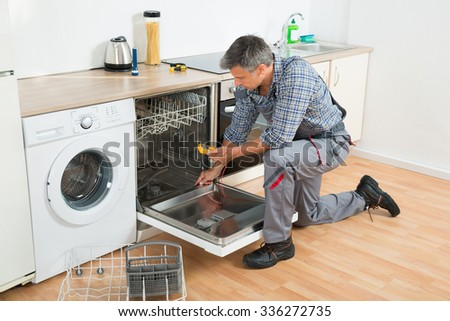 Full length of repairman checking dishwasher with digital multimeter in kitchen - stock photo