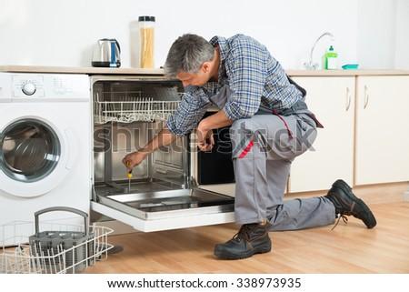 Full length of repairman repairing dishwasher with screwdriver in kitchen - stock photo