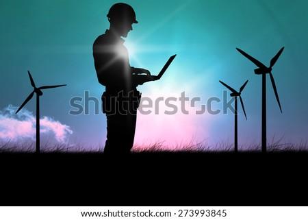 Full length of repairman using laptop against magical sky - stock photo