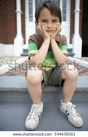 Full length of sad little boy with hands on chin sitting on front steps of house - stock photo