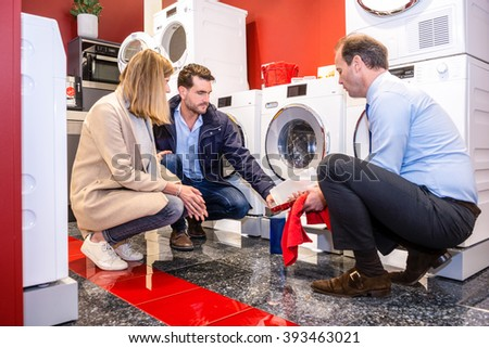 Full length of salesman explaining product to customers in washing machine department of hypermarket - stock photo