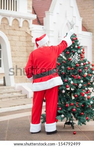Full length of Santa Claus decorating Christmas tree outside house - stock photo