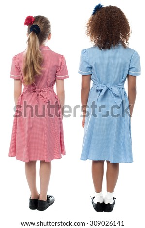 Full length of school girls in uniform facing the wall - stock photo