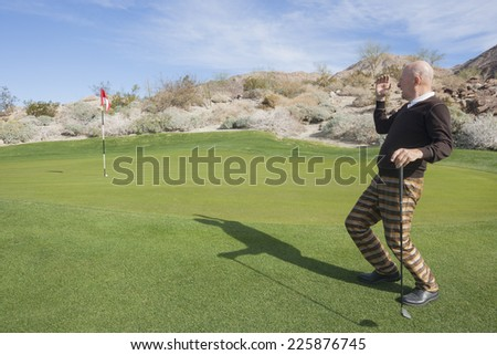 Full length of senior male golfer looking away at golf course - stock photo