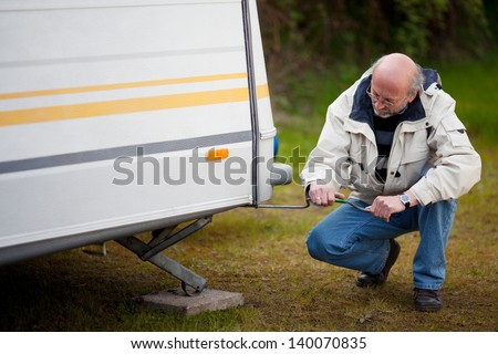 Full length of senior man crouching while repairing caravan in forest - stock photo