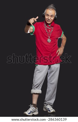 Full length of senior man with rock and roll sign - stock photo