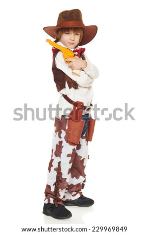 Full length of serious little boy in a suit of the cowboy posing with guns, on a white background - stock photo