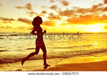 Full length of silhouette young woman jogging on shore. Side view of determined mixed race Asian / Caucasian female is running during sunrise. She is representing her healthy lifestyle. - stock photo