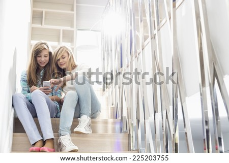 Full-length of sisters listening to music on stairway - stock photo