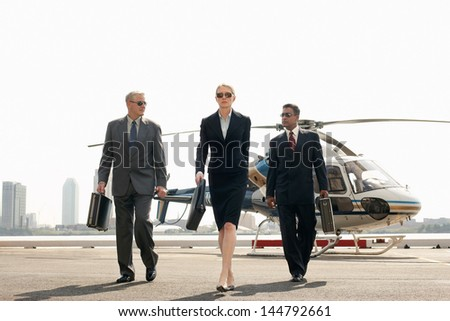 Full length of smart multiethnic businesspeople arriving from helicopter - stock photo