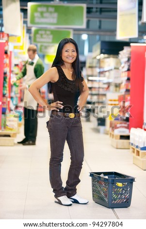 Full length of smiling asian woman looking at camera with hands on waist and man in the background - stock photo