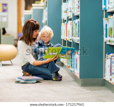 Full length of smiling boy and teacher reading book by bookshelf in library - stock photo