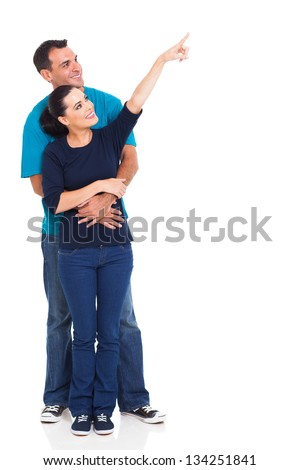 full length of smiling boyfriend and girlfriend pointing away isolated on white - stock photo