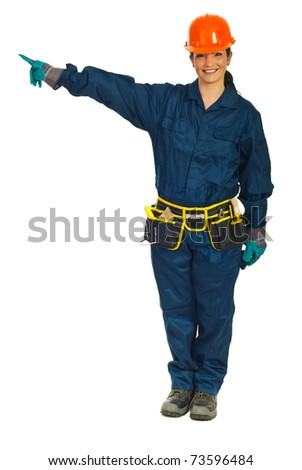 Full length of smiling constructor worker woman pointing in left part of image to copy space against white background