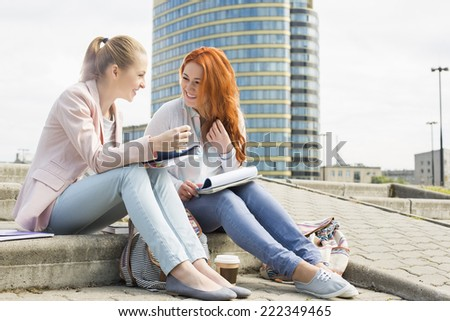 Full length of smiling female college students studying on steps against building - stock photo