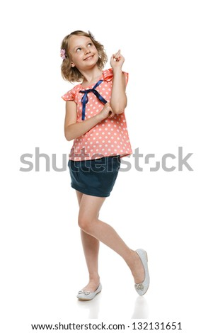Full length of smiling little girl pointing and looking up, over white - stock photo