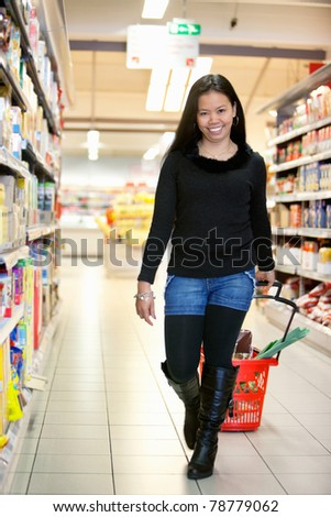 Full length of smiling woman in shopping centre pulling basket while walking and looking at camera - stock photo