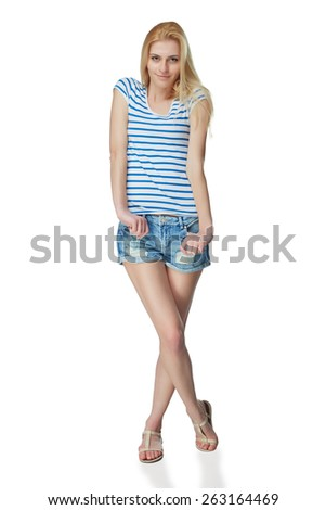 Full length of smiling young slim tanned female in denim shorts standing with crossed legs, isolated on white background
