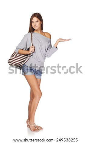 Full length of smiling young slim tanned female in denim shorts with beach bag showing open hand palm with copy space for product or text, isolated on white background - stock photo