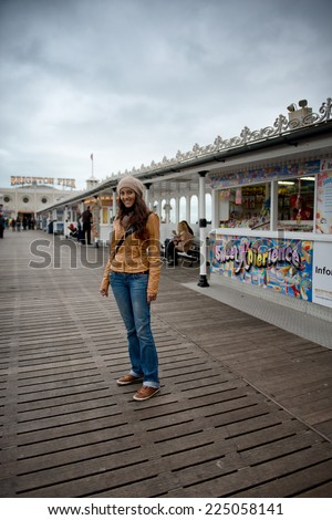 Full Length of Smiling Young Woman Wearing Warm Clothing Standing on Brighton Pier, England - stock photo