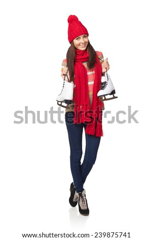 Full length of smiling young woman wearing warm hat and scarf carrying a pair of ice skates, over white background - stock photo