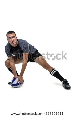 Full length of sports player in black jersey stretching with ball against white background