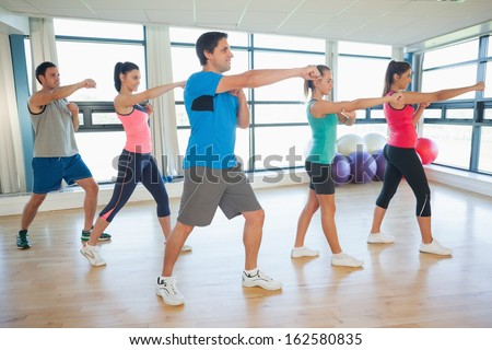Full length of sporty people doing power fitness exercise at yoga class - stock photo