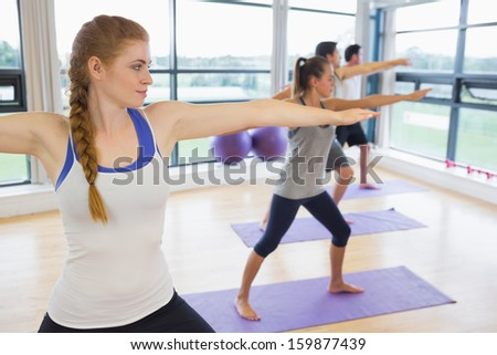Full length of sporty people stretching hands at yoga class in fitness studio
