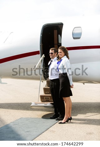 Full length of stewardess and pilot standing against private jet - stock photo