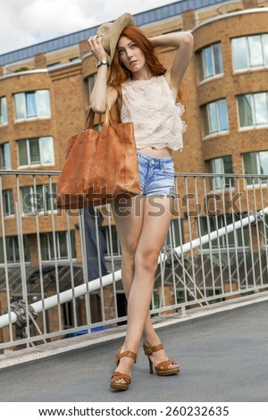 Full Length of Stylish Young Woman with Gorgeous Face Holding Big Brown Leather Bag Leaning on Rail Fence