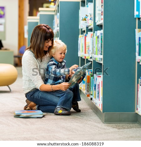 Full length of teacher and schoolboy reading book by bookshelf in library - stock photo