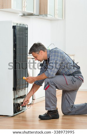 Full length of technician checking fridge with multimeter at home