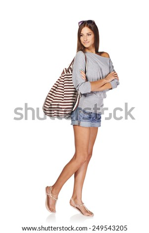 Full length of thinking young slim tanned female in denim shorts with backpack and sunglasses looking away at blank copy space, isolated on white background - stock photo