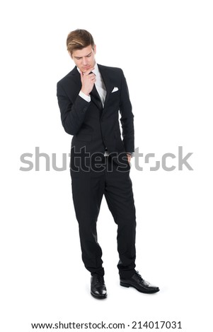Full length of thoughtful businessman with hand on chin standing over white background - stock photo