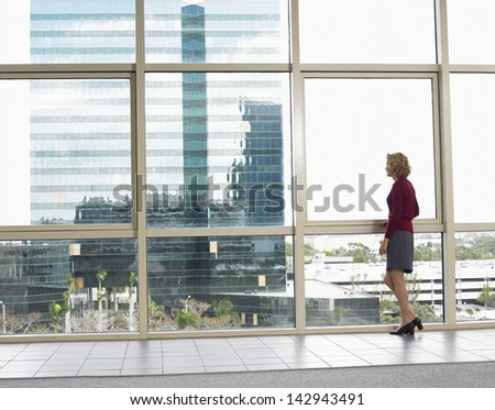 Full length of thoughtful businesswoman looking out of office building - stock photo