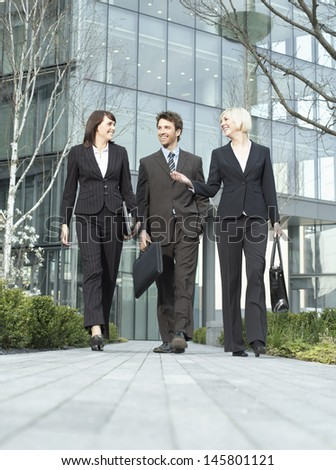 Full length of three business people walking outside office building - stock photo