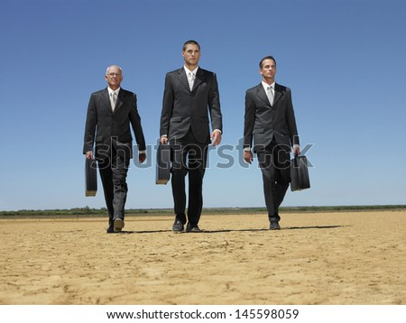 Full length of three businessmen with briefcases walking in desert - stock photo