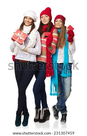 Full length of three friends girls wearing winter hats, mufflers and gloves showing blank red cards and gift box over white background - stock photo