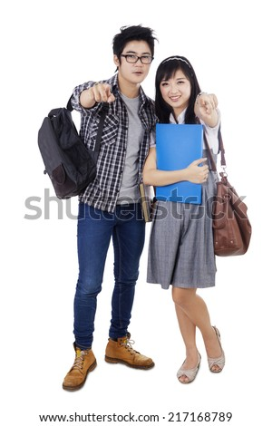 Full length of two asian students standing in studio and pointing at camera - stock photo