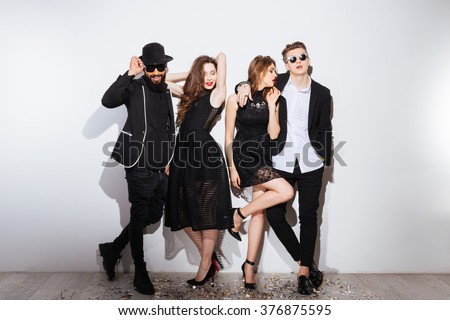 Full length of two beautiful young couples standing and posing over white background - stock photo