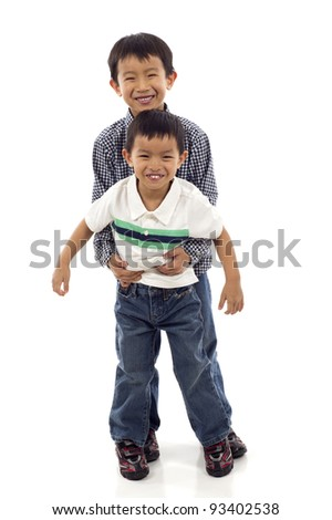 Full length of two boys, siblings, brothers and best friends having fun isolated over white background - stock photo