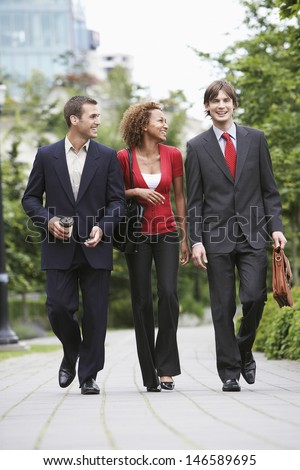 Full length of two businessmen and woman walking through city park