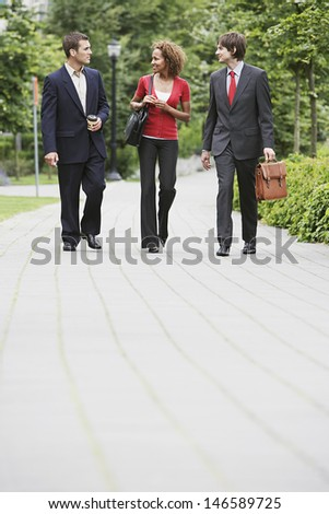Full length of two businessmen and woman walking through city park - stock photo