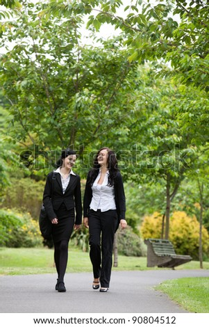 Full length of two female executives walking in park - stock photo