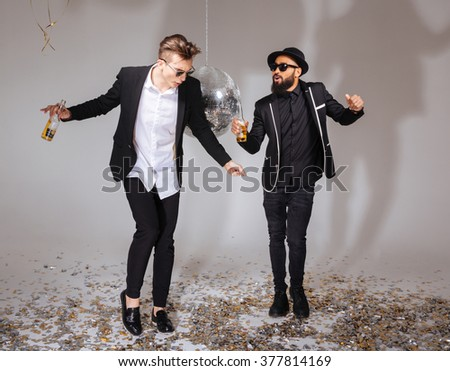 Full length of two handsome male friends in black suits and sunglasses dancing and drinking beer over white background - stock photo