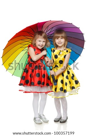 Full length of two little girls standing under umbrella over white background - stock photo