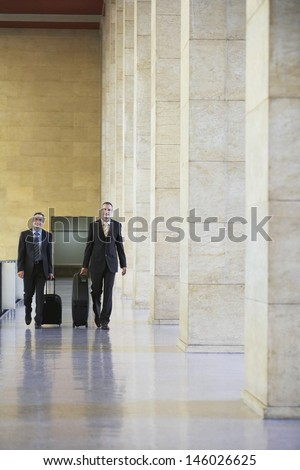 Full length of two smiling businessmen pulling luggage in airport lobby - stock photo