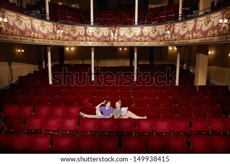 Full length of two young women sitting in theatre stall with scripts - stock photo