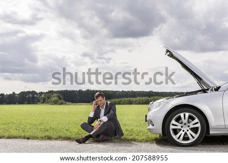 Full length of unhappy young businessman using cell phone by broken down car at countryside - stock photo