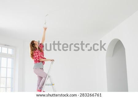 Full-length of woman on ladder fitting light bulb in new house - stock photo